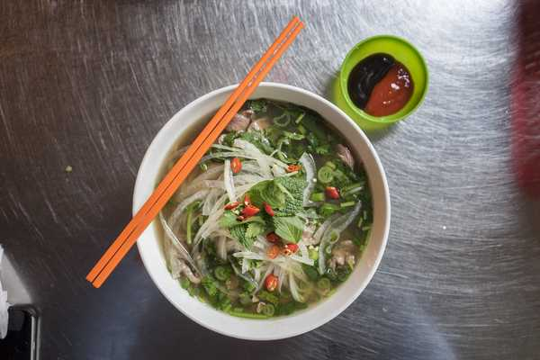 Delicious bowl of Pho Tai with fresh herbs and chili