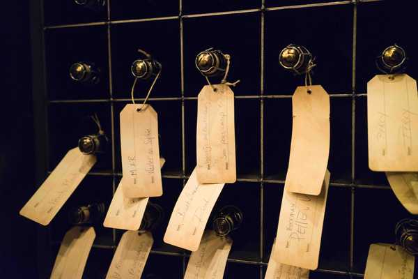 Bottles of craft beer aging with their owners' hand written tags