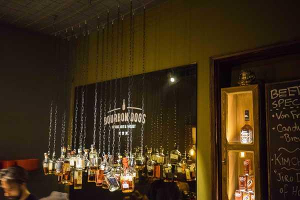 Bourbon bottles hang from the ceiling